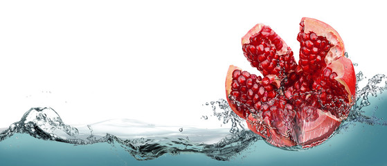 Pomegranate fruit in spray of water.