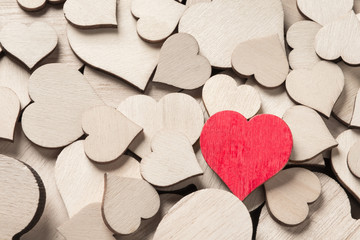 One wooden painted red heart among many colorless wooden hearts