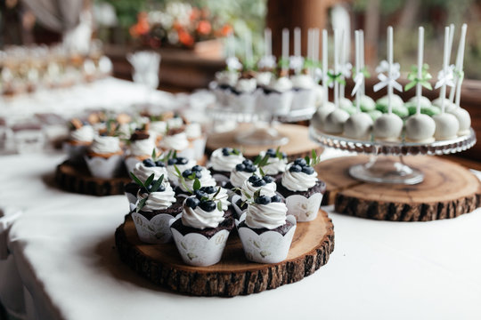 Mahy cupcakes decorated with cream and berries on a plate and wood