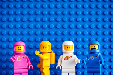 Tambov, Russian Federation - February 24, 2019 Four Lego astronaut minifigures against blue baseplate background. The LEGO Movie 2.