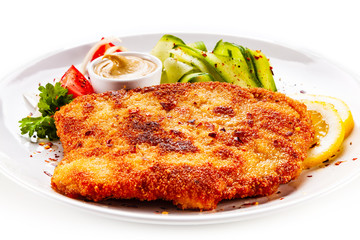 Fried pork chop and vegetable salad on white background
