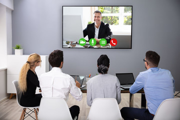 Businesspeople Discussing Graphs Through Videochat