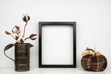 Mock up black frame with cotton branch and plaid pumpkin decor on a shelf or desk. Autumn concept. Portrait frame against a white wall.
