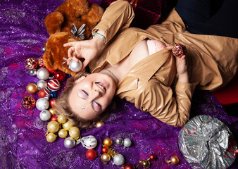 Top view of a young woman lying on the floor surrounded with nicely christmas toys balls and wrapped present