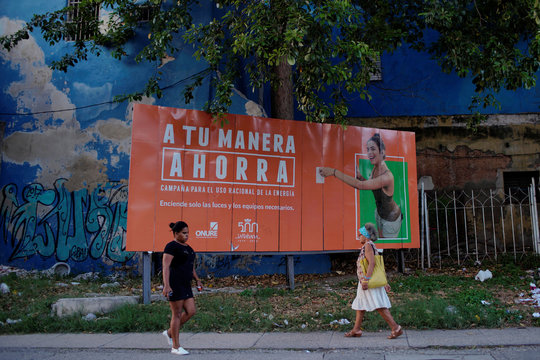 People pass by a billboard used in a governmental campaign to save energy in Havana