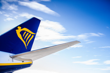 Valencia, Spain - March 8, 2019: Tail of a plane of the Ryanair travel company, isolated with blue cloud background.