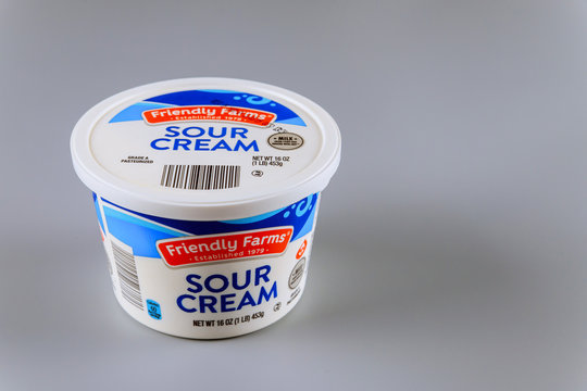 Plastic container of sour cream, produced by Friendly Farms USA on a gray isolated background