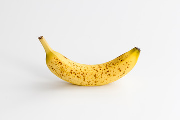 Single ripe banana with brown spots centered and isolated on a white background.