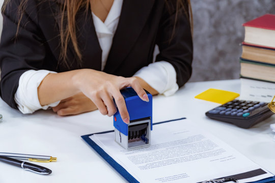 woman notary stamping document at table, close up.