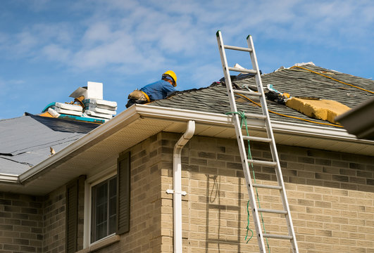 Roof worker installing new shingles on a roof of a house