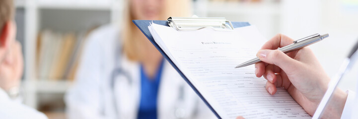 Female medicine doctor hand holding silver pen looking in clipboard pad closeup. Ward round patient...