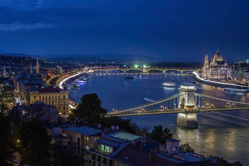 Budapest, Hungary - Illuminated Szechenyi Chain Bridge on a night photograph with Parliament of Hungary, moving ships on River Danube and clear dark blue sky after sunset