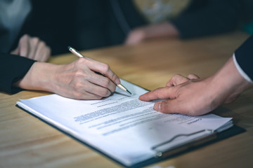 Business contract signing - Man pointing at the bottom at the contract for a woman for signature.