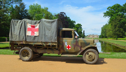 Vintage Second World War truck with red cross signs  parked  with Wrest Park House in background