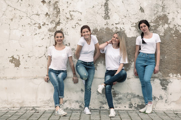 Group of diverse girls in tshirts and jeans over street wall