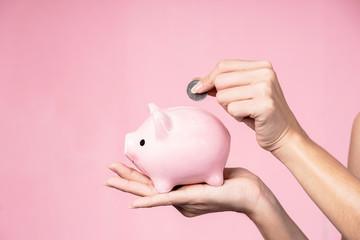 Closeup of hands putting coin into a piggy bank. Saving concept.