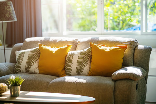 Vintage sofa and pillows in living room with sunlight in the morning. Relax corner concept.