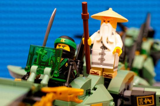 Tambov, Russian Federation - August 19, 2017 Lego Ninjago Movie. The Green Ninja and Wu flying on Green Ninja Mech Dragon. Blue background. Studio shot.