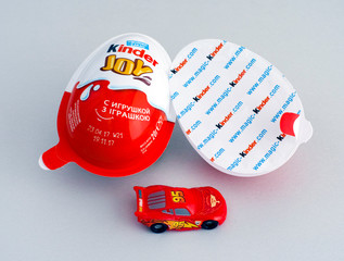 Tambov, Russian Federation - June 01, 2017 Kinder Joy eggs with Lightning McQueen car toy on gray background. Kinder Joy manufactured by Italian company Ferrero. Studio shot.