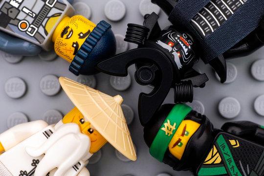 Tambov, Russian Federation - August 19, 2017 Four Lego Ninjago Movie minifigures - The Green Ninja, Wu, Garmadon and Charlie - on gray baseplate background. Studio shot.