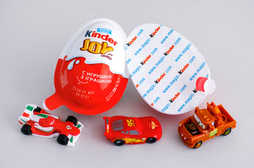 Tambov, Russian Federation - June 01, 2017 Kinder Joy eggs with three Kinder Ð¡ars toys on gray background. Kinder Joy manufactured by Italian company Ferrero. Studio shot.