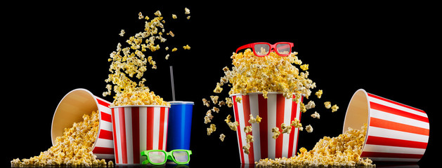 Paper striped bucket with popcorn, cup of drink and glasses isolated on black