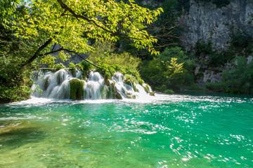 Rushing water cascades down the natural barriers into the crystal clear and azure coloured Lake Gavanovac at the Plitvice Lakes National Park, Croatia Wall mural