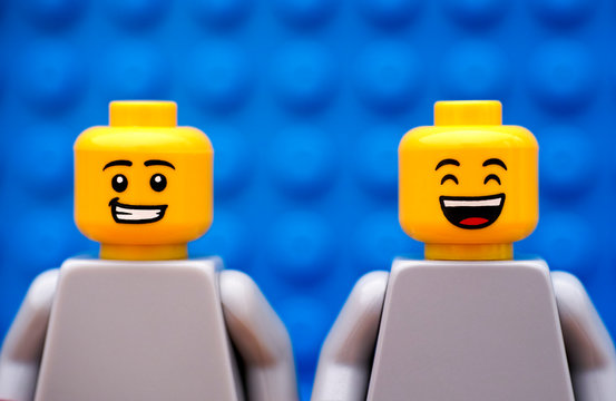 Tambov, Russian Federation - July 24, 2016 Two Lego minifigures - one with smirk and one happy. Blue background. Studio shot.