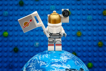 Tambov, Russian Federation - July 06, 2016 Lego spaceman minifigure with flag stay on planet against Lego blue baseplate with stars. Studio shot.