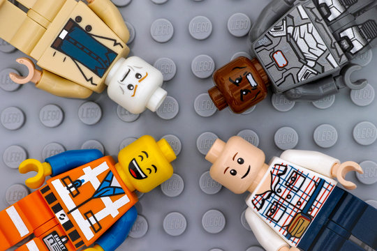 Tambov, Russian Federation - July 06, 2016 Four Lego minifigures with with different color heads and different emotions on faces on Lego gray baseplate background.