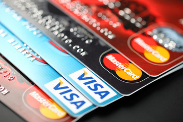 Tambov, Russian Federation - September 11, 2012: Heap of credit cards with Visa and Mastercard logos on black background. Studio shot.