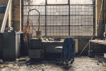 Vieux bureau dans une usine avec un plante morte