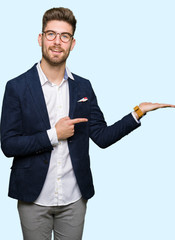 Young handsome business man wearing glasses amazed and smiling to the camera while presenting with...