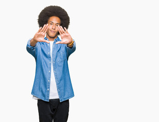 Young african american man with afro hair Smiling doing frame using hands palms and fingers, camera perspective