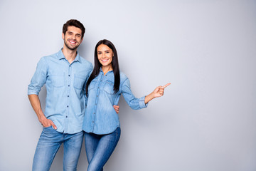 Fototapeta Photo of cheerful trendy charming brown haired nice cute couple of two people pointing at emptiness away wearing jeans denim jackets isolated over grey color white background