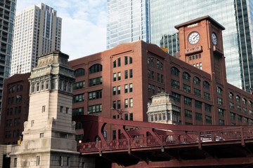 Chicago red bricks buiklding with a clock tower over red bridge