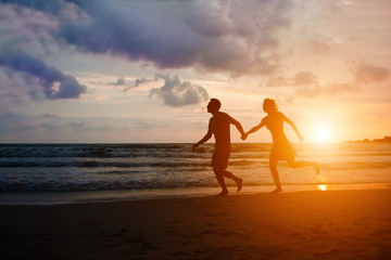 Happy couple running at sunset sea beach with holding hands. Honeymoon travel for spouses to tropical paradise country. Man and woman in love have fun in evening sunshine.