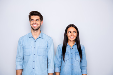 Photo of cute cheerful brown haired charming couple of spouses feeling awkward smiling toothily wearing jeans denim isolated over grey color background Wall mural