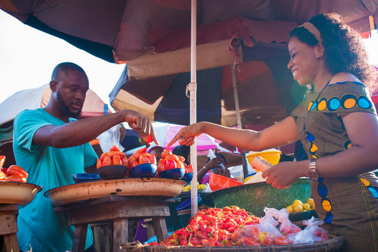 Black girl choosing tomatoes from a local market seller. man selling tomatoes to a young woman