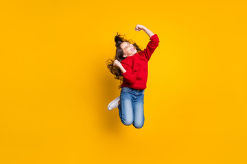 Full length photo of delighted crazy girl jump raise fists scream yeah celebrate victory in lottery challenge feel lucky wear style pullover denim clothes sneakers isolated yellow color background