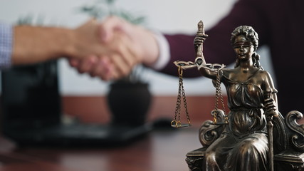 Statuette of lady justice on the table close-up on a blurred background of two men handshaking Wall mural