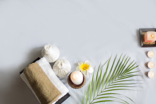 Spa treatments on White spa massage bed with candles, massage oil and Herbal massage cubes