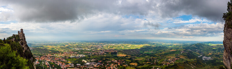Panoramic view of the Italian countryside and Adriatic Sea (Riviera Romagnola) from Republic of San Marino with the oldest tower (Guaita fortress) on Mount Titan (Monte Titano) on the left Wall mural