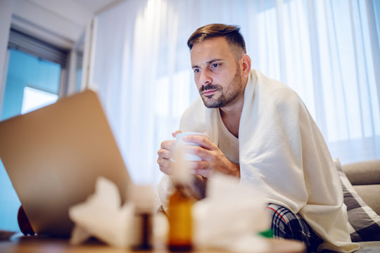 Sick serious employee in pajamas covered with blanket drinking tea and looking at laptop while sitting on sofa in living room.