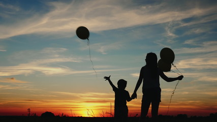 Silhouette two children with balloons at sunset. The little boy lets go of the balloon to the sky. Bright beautiful sky with clouds