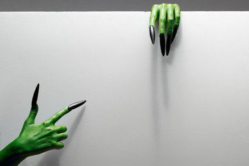 Halloween concept. Two green hands hold gray sheet of paper.