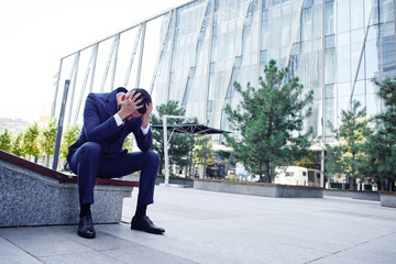 Financial ruined desperate businessman at the entrance to a glass office building, concept of bankruptcy