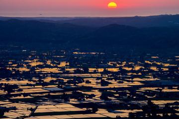 富山県南砺市八乙女山から望む散居村と日本海に沈む夕日