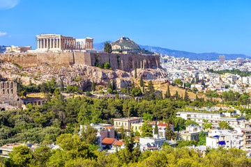 Fototapete - Athens in summer, Greece. Famous Acropolis hill rises above cityscape. It is top landmark of Athens. Scenic view of Ancient Greek ruins. Landscape of old Athens city with Parthenon. Skyline of Athens.