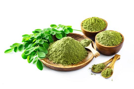 Moringa powder (Moringa Oleifera) in wooden bowl with original fresh Moringa leaves isolated on white.